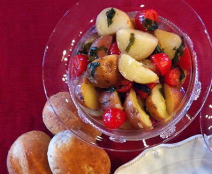 Warm potato salad with cherry tomatoes and fresh basil
